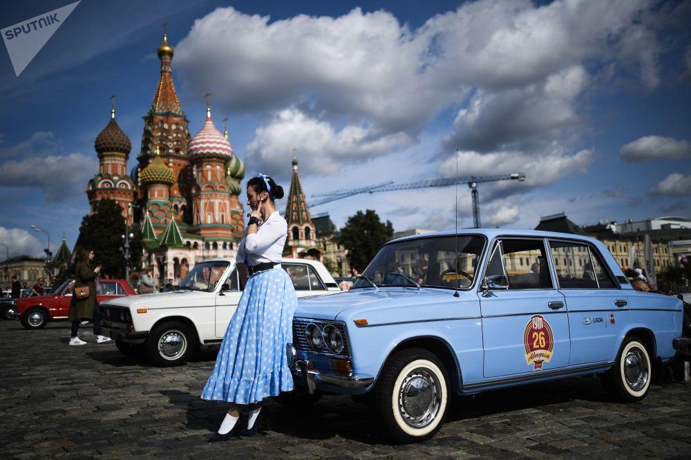 دختری در کنار ماشین ژیگولی قدیمی تولید شده در زمان شوروی