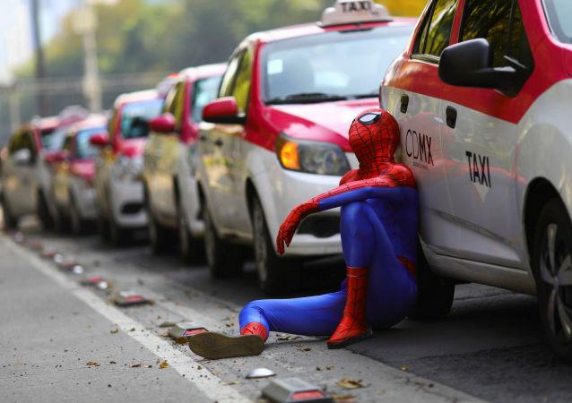 مردی با لباس مرد عنکبوتی کنار تاکسی در تظاهرات تاکسی ها علیه برنامه های درخواست تاکسی اینترنتی در مکزیک