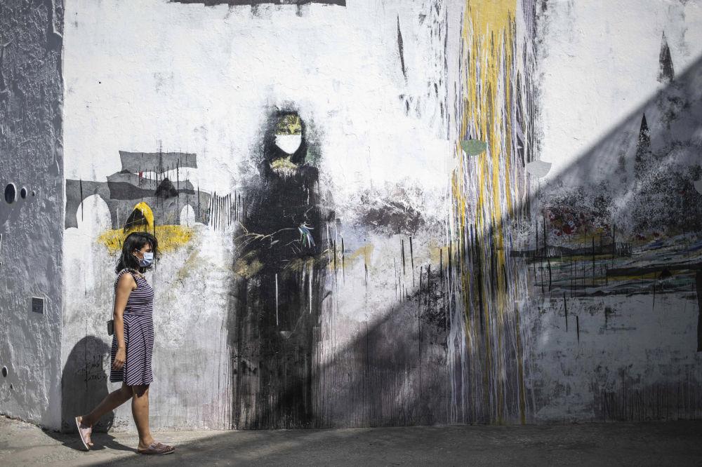 زنی با ماسک در کنار گرافیتی مونالیزا در مراکش