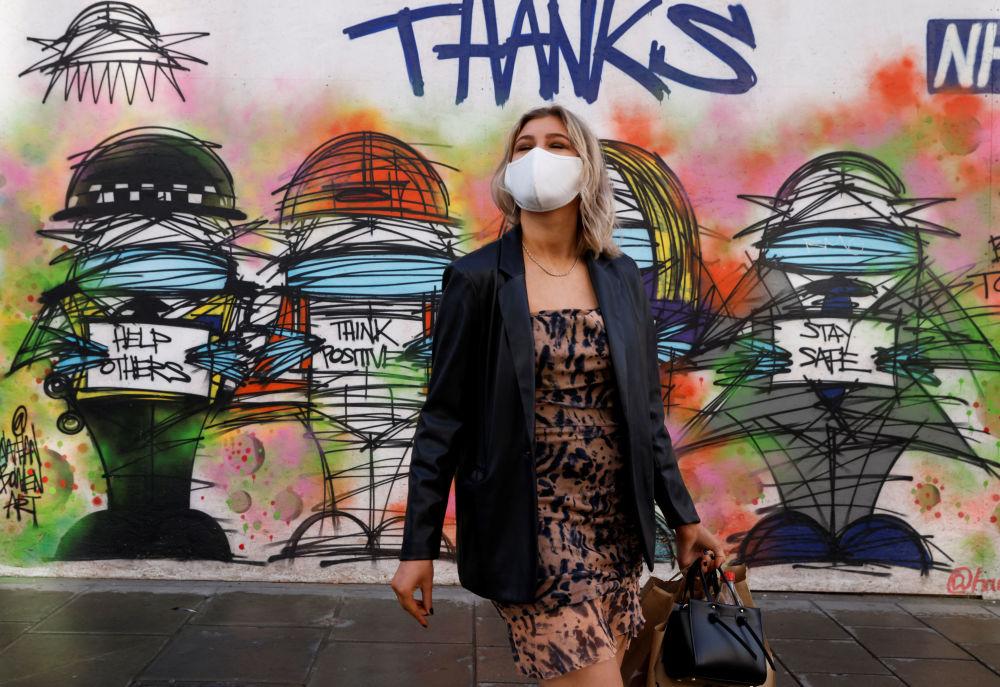 دختری با ماسک در کنار گرافیتی در لندن