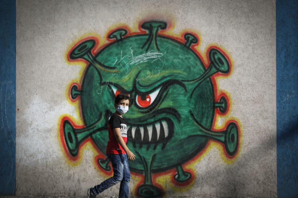 پسری در کنار گرافیتی ویروس کرونا در غزه فلسطین