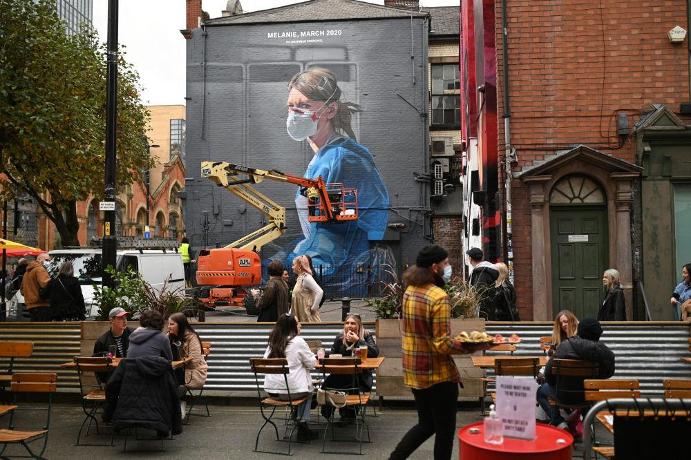 مردم در کنار گرافیتی پرستار در منچستر