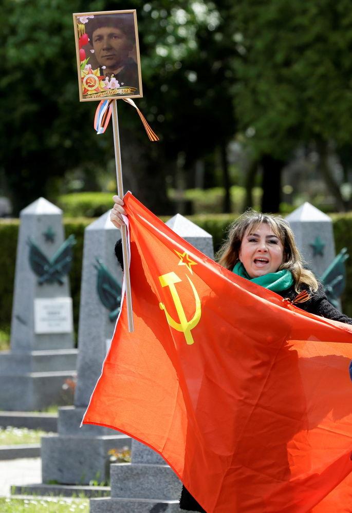 زنی با پرچم شوروی و تصویر یک جانباز در قبرستان اولشانسکی در پراگ، جمهوری چک