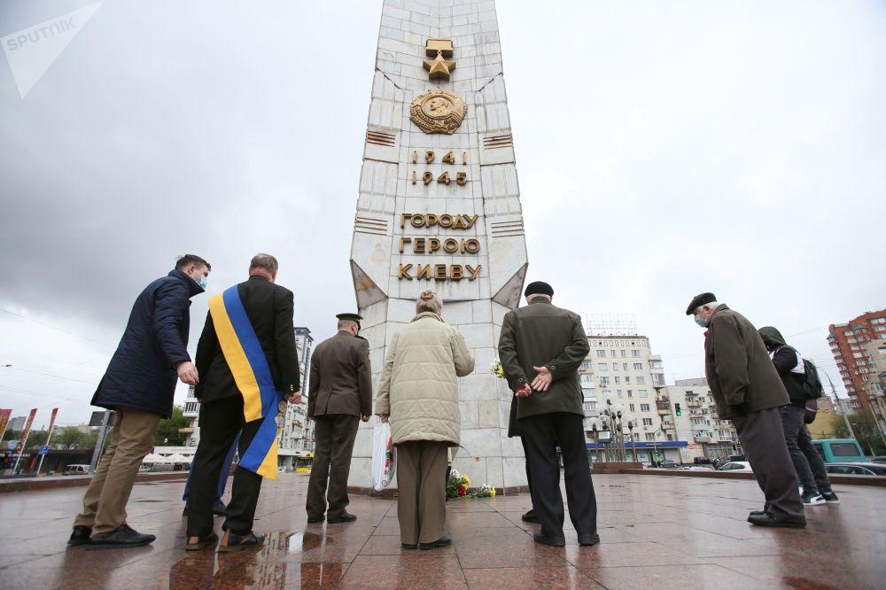 مردم به ابلیسک شهر قهرمان پرور کی یف در میدان پیروزی گل هدیه میکنند