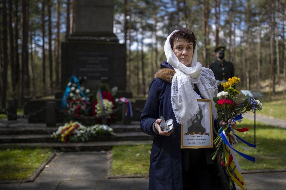 زنی با تصویر یک جانباز در بنای یادبود پانرای در ویلنیوس در مراسم هفتاد و ششمین سالگرد پایان جنگ جهانی دوم