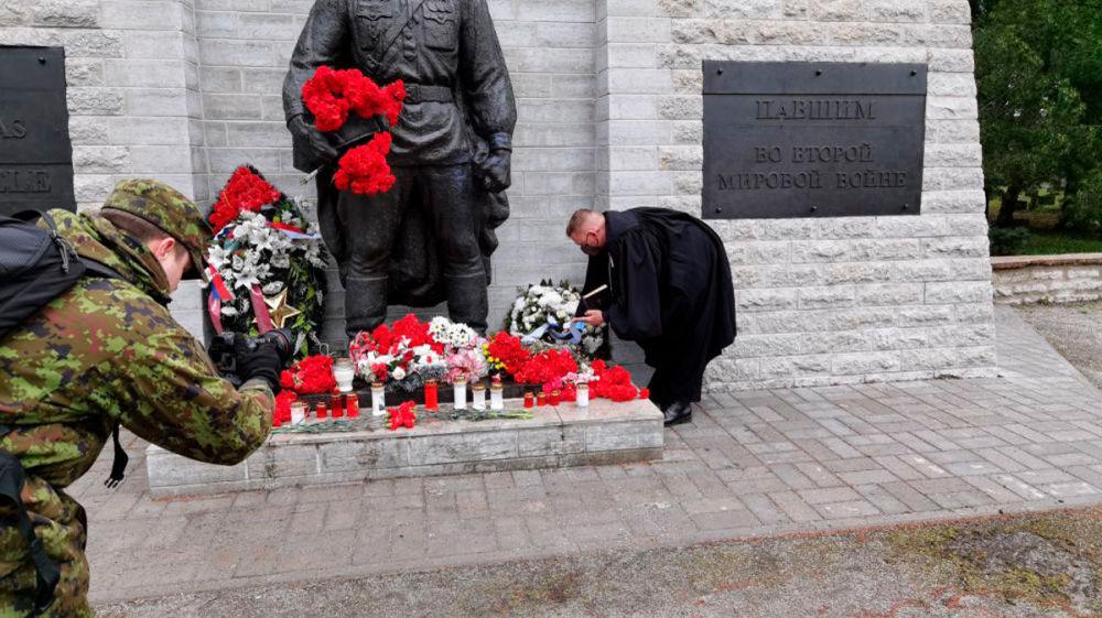 تقدیم تاج گل توسط روحانی نیروهای دفاعی استونی به یادبود جانباختگان در جنگ جهانی دوم در قبرستان نظامی تالین