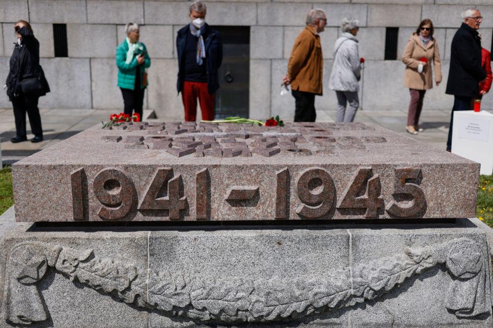 تقدیم گل توسط مردم به مناسبت هفتاد و ششمین سالگرد پایان جنگ جهانی دوم به یادبود جنگ شوروی در پارک ترپتاو برلین