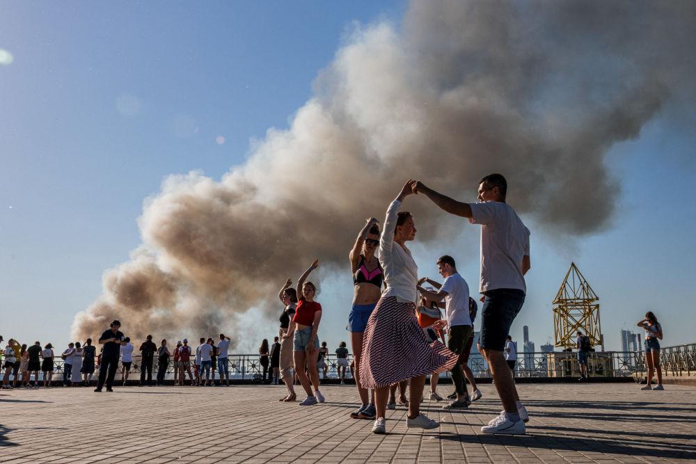 رویدادهای هفته به روایت تصویر  رقص سامبا در زمینه دودی که از آتش سوزی انباری در مسکو بلند شده است