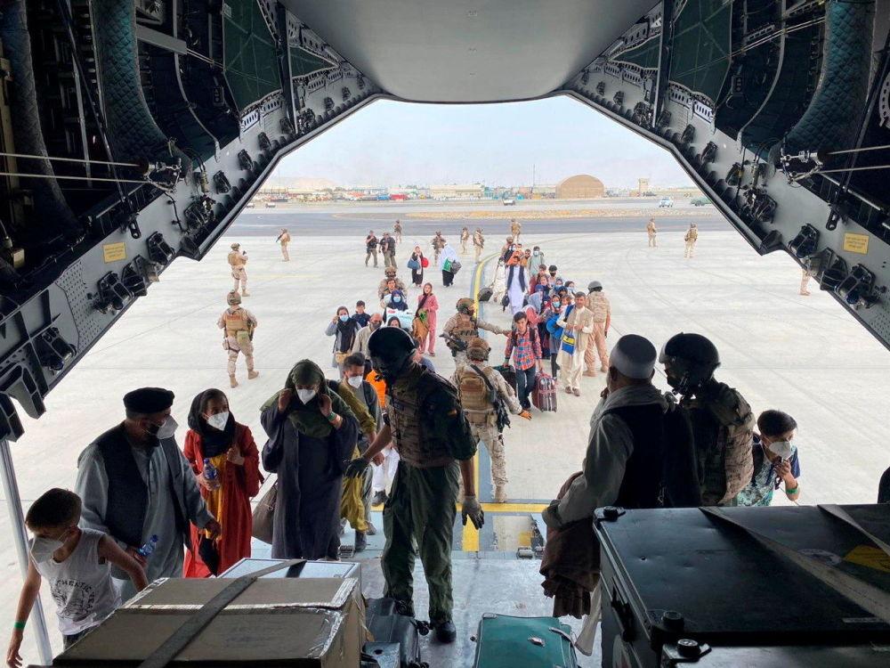 شهروندان اسپانیایی و افغانستانی در حین سوار شدن به هواپیمای نظامی در فرودگاه بین المللی حامد کرزی در کابل