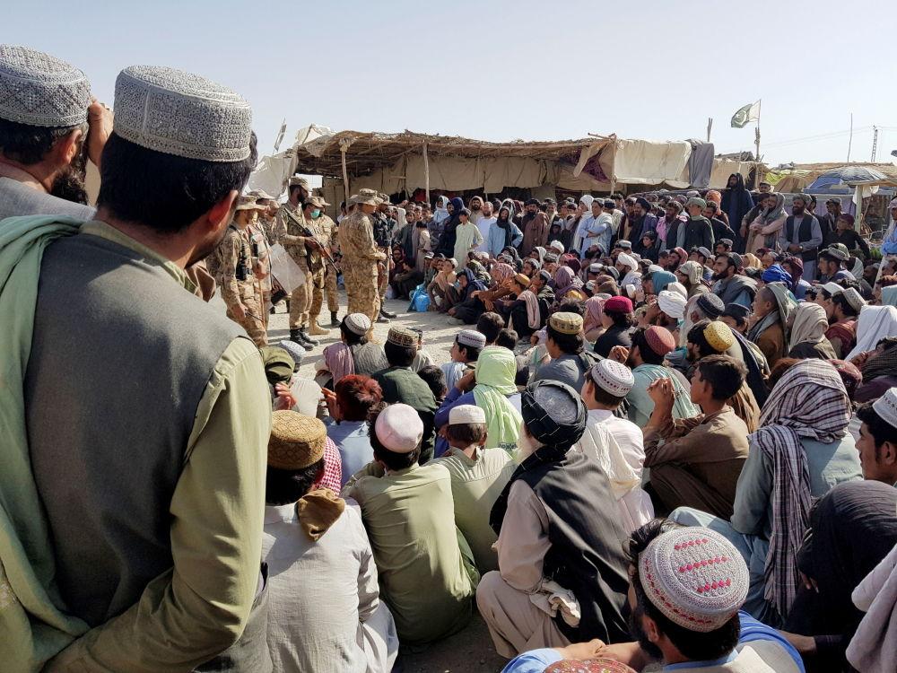 سربازان ارتش پاکستان در حال صحبت با مردم در مورد عبور از ایست بازرسی در شهر چمن واقع در مرز پاکستان و افغانستان