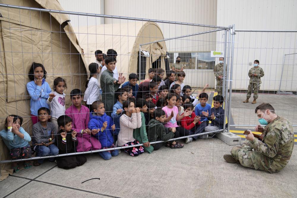 گیتار نوازی سرباز آمریکایی برای کودکان پناهجوی  افغان در پایگاه هوایی رامشتاین در آلمان