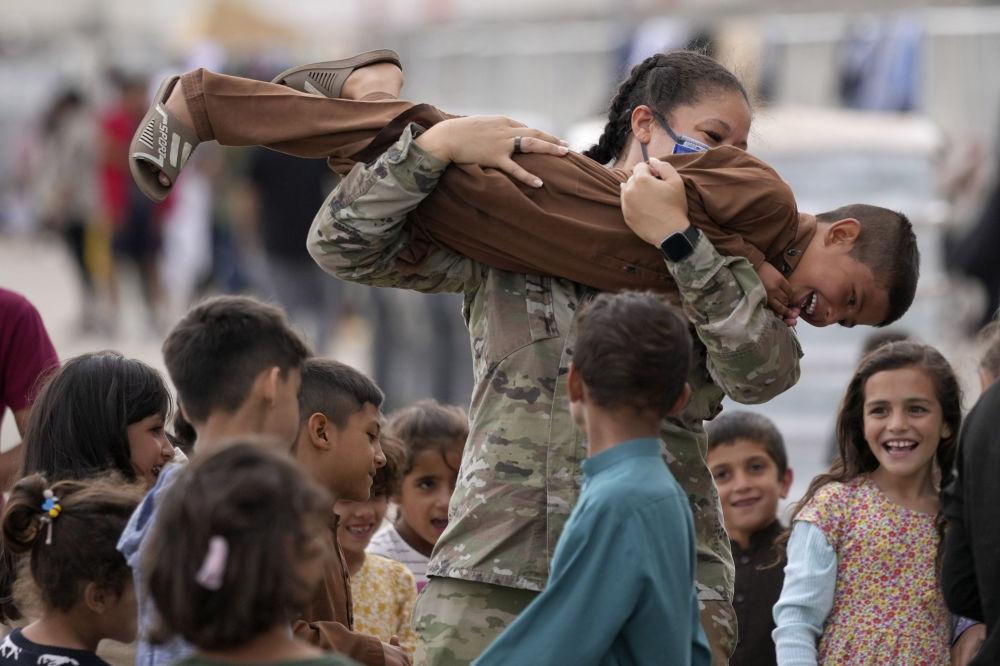 سرباز آمریکایی با کودکان پناهجوی  افغان در پایگاه هوایی رامشتاین در آلمان بازی می کند
