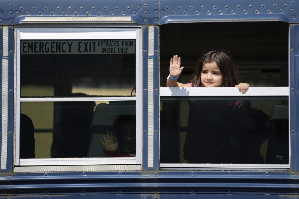 کودک افغان در یکی از اتوبوس ها در پایگاه هوایی رامشتاین در آلمان دست تکان می دهد