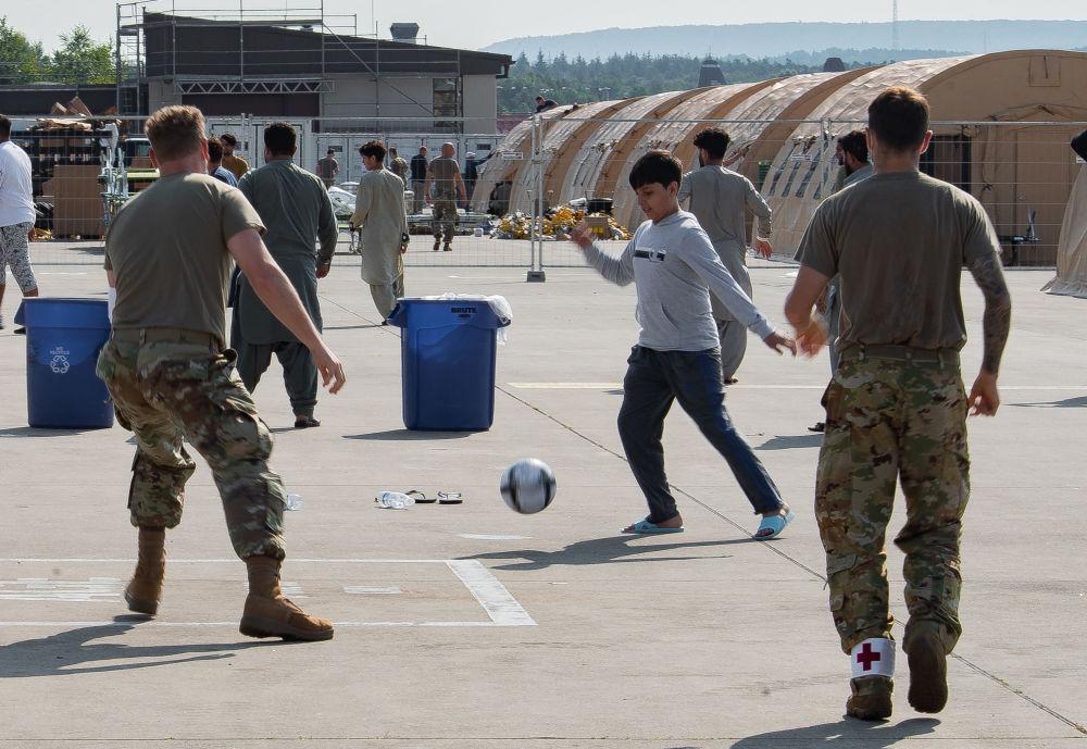 خلبانان نیروی هوایی آمریکا با کودکان پناهجوی  افغان در پایگاه هوایی رامشتاین در آلمان فوتبال بازی می کنند