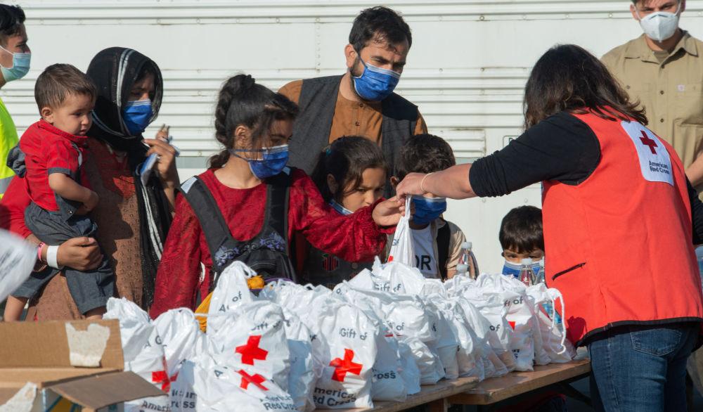 نمایندگان صلیب سرخ در میان پناهپویان افغان در پایگاه هوایی رامشتاین در آلمان کمک های اانسانی توزیع می کنند
