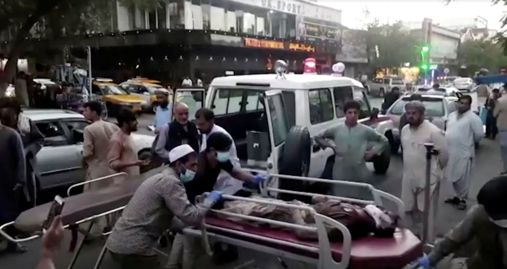مردم زخمی ها را پس از حملات تروریستی به فرودگاه کابل به بیمارستان می رسانند
