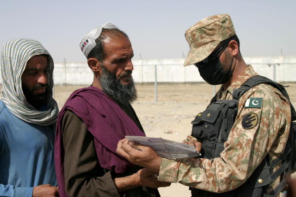 سرباز پاکستانی اسناد پناهجویان افغان را در مرکز ایست بازرسی در نزدیکی شهر مرزی چمن پاکستان بررسی می کند