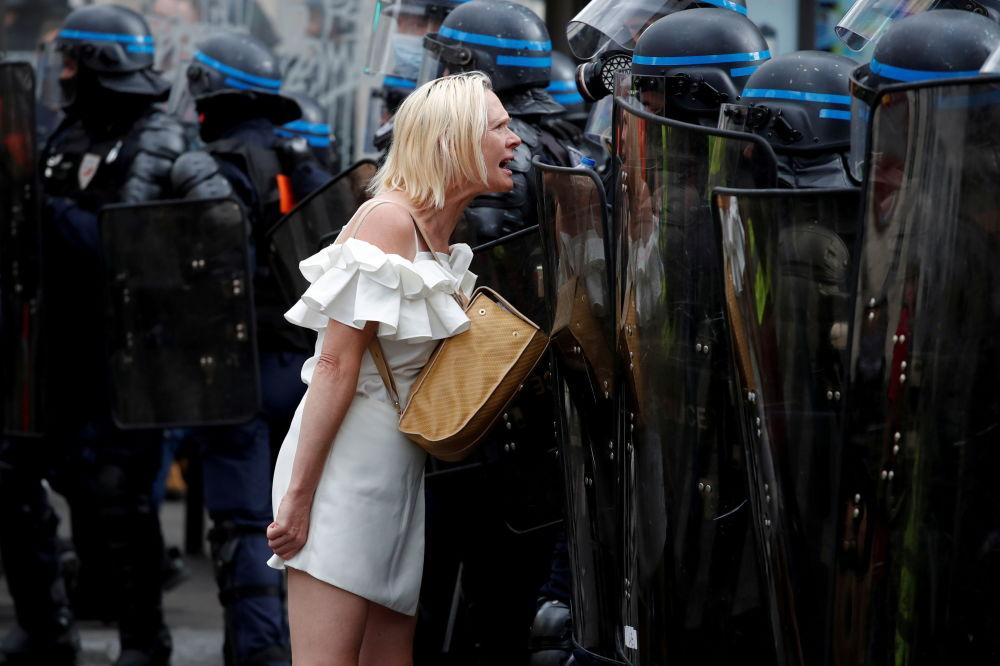 زنی در مقابل مامور پلیس در تظاهرات پاریس