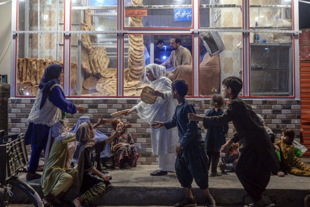 زنی در مقابل نانوایی در کابل بین کودکان نیازمند نان تقسیم می کند