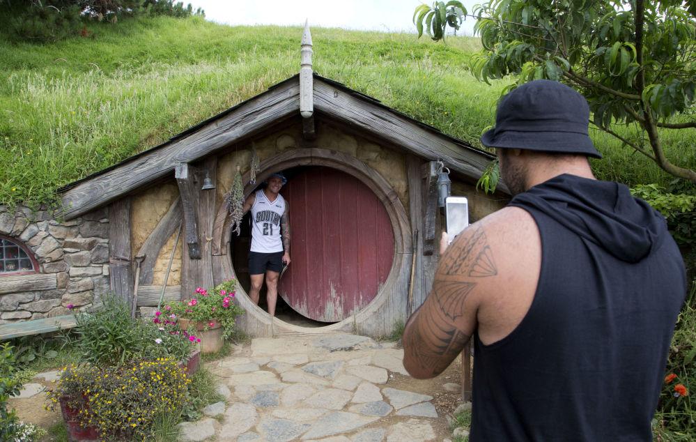 توریست ها در حال عکاسی از محل فیلم برداری «هابیت» در نیوزیلند