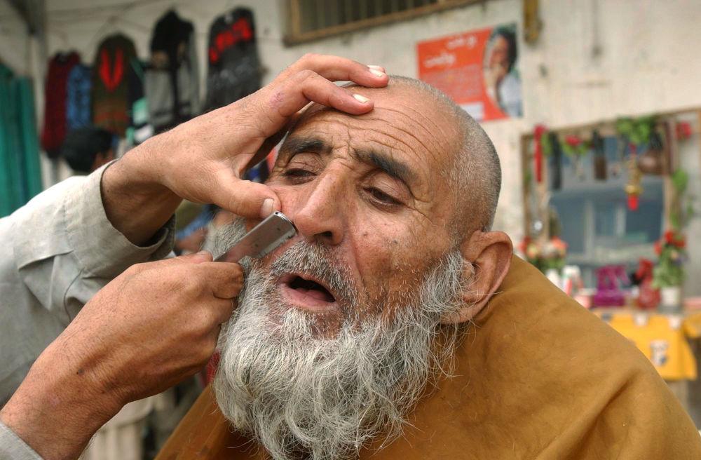 آرایشگر خیابانی که در جلال آباد سال ۲۰۰۶ اصلاح می کند