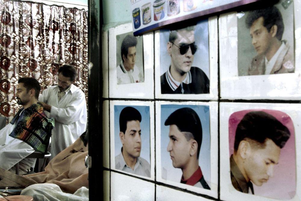 در یک آرایشگاهی در کابل سال ۲۰۰۲، عکس هایی روی دیوار آویزان شده است که سبک های مختلف موهای بدون ریش را نشان می دهد