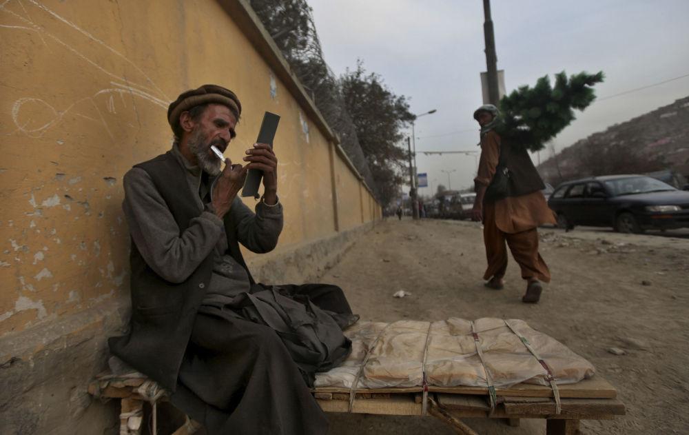 یک آرایشگر کنار جاده در کابل سال ۲۰۱۰ در حالی که منتظر مشتری است، ریش خود را می زند