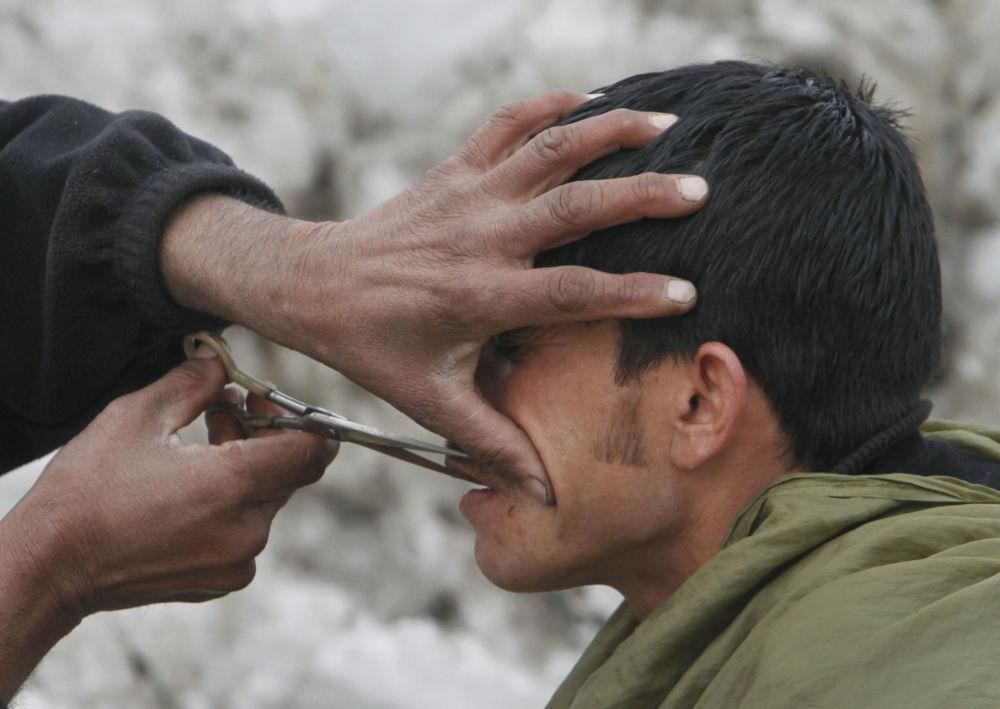 آرایشگر خیابانی که در کابل سال ۲۰۱۲ اصلاح می کند