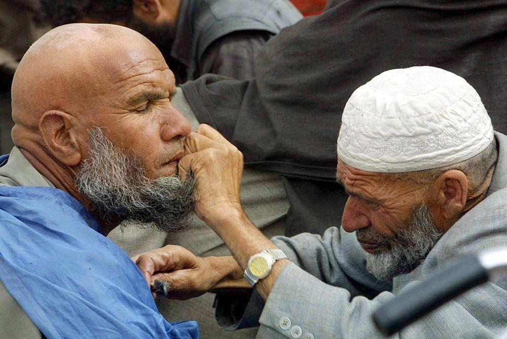 آرایشگر خیابانی که در کابل سال ۲۰۰۲ اصلاح می کند