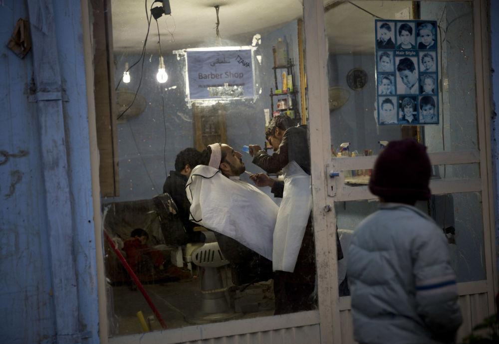 پسری به آرایشگاهی در کابل سال ۲۰۱۳ نگاه می کند که در آن ریش مردی در حال کوتاه شدن است