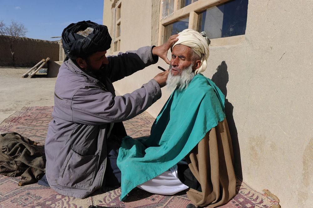 آرایشگر روستایی در حال زدن ریش مردی در ولایت غزنی افغانستان در سال ۲۰۱۱