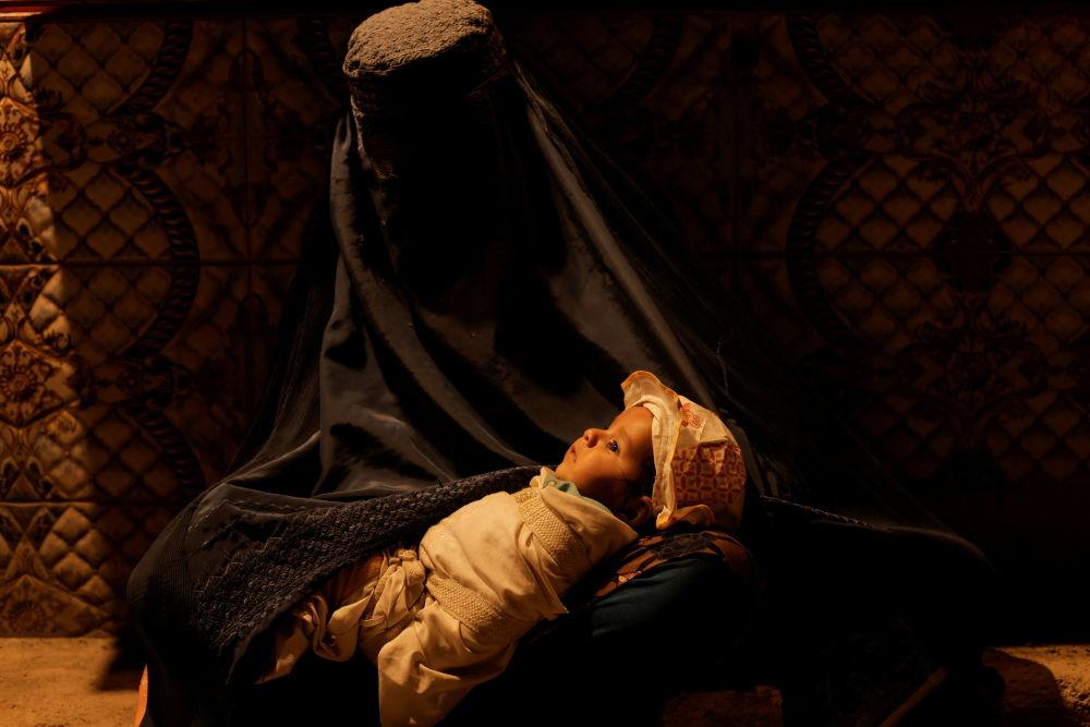 زن افغان با چهره پوشیده و کودکی در آغوش