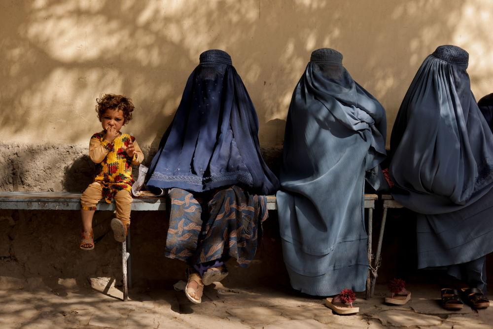 کودکی در کنار زنان چادری افغان در کنار بیمارستانی در کابل