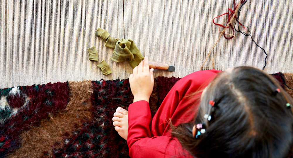 دختر ترکمن در حال تمرین قالی بافی
