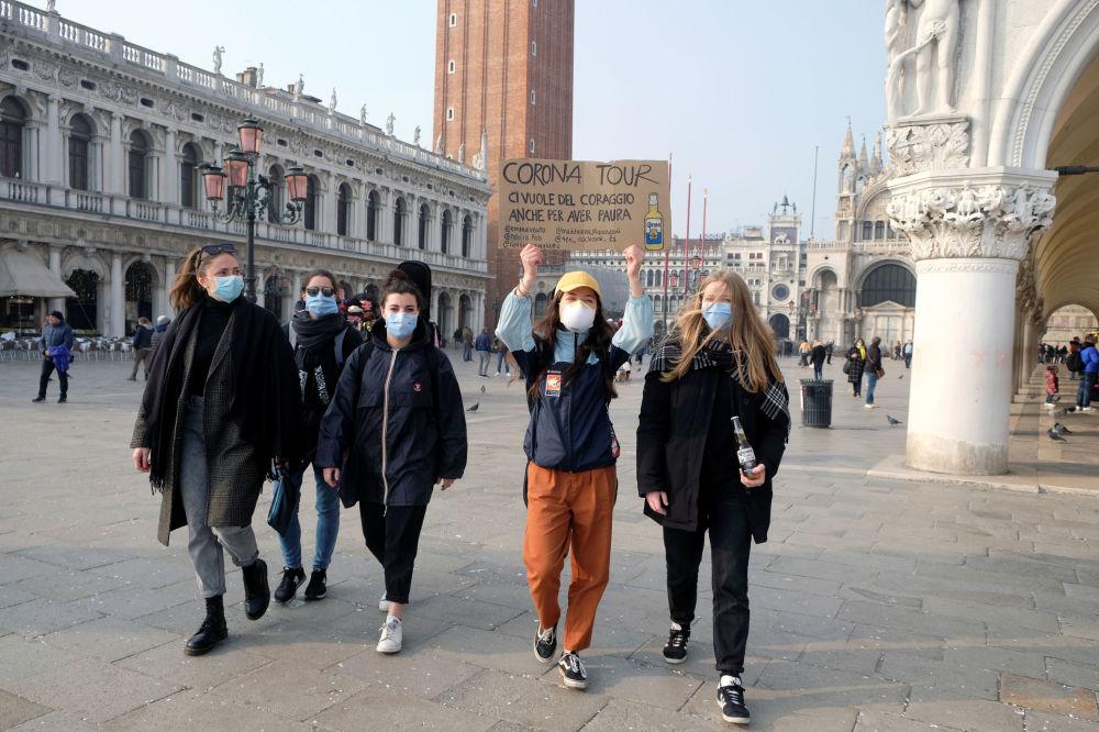 Группа девушек в защитных масках идет по площади Сан-Марко в Венеции с плакатом Корона-тур. Надо иметь смелость, даже чтобы бояться, после того, как последние дни Венецианского карнавала были отменены из-за вспышки коронавируса на севере Италии