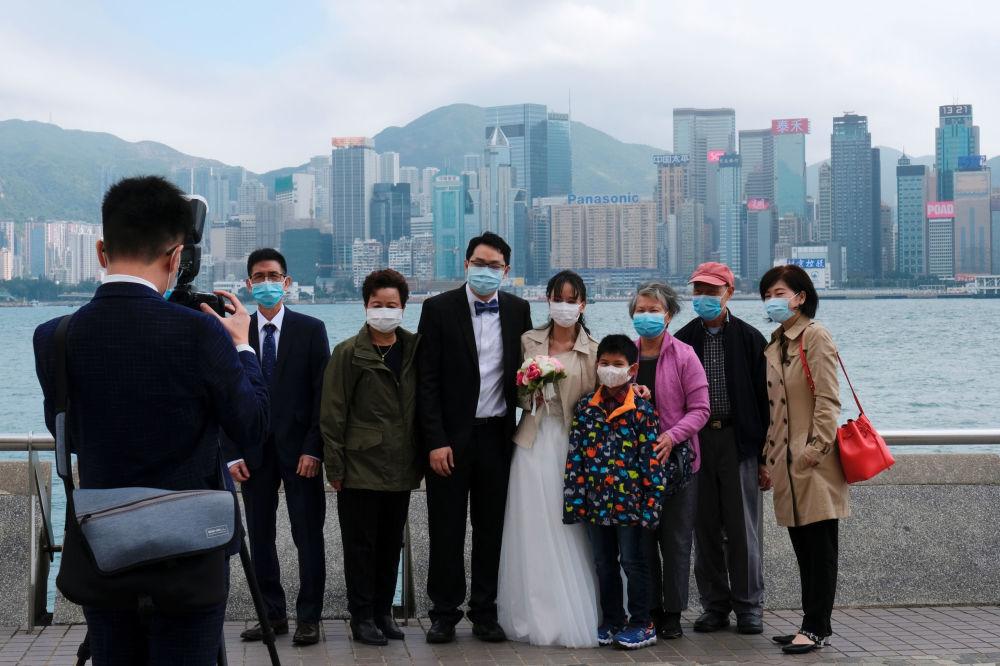 Опасность распространения болезни изменила поведение людей. На снимке - молодожены в защитных масках фотографируются с семьей на память после регистрации брака в районе Цим Ша Цуй в Гонконге, Китай