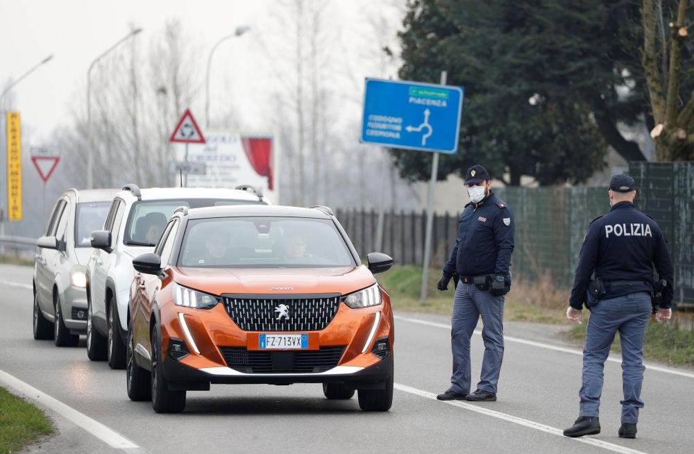 Сотрудники итальянской полиции тоже одели средства защиты. На снимке - полицейские в масках предупреждают водителей о закрытии дороги между Кодоньо и Казальпустерленго. Ограничение на движение машин было введено из-за вспышки коронавируса в северной Италии