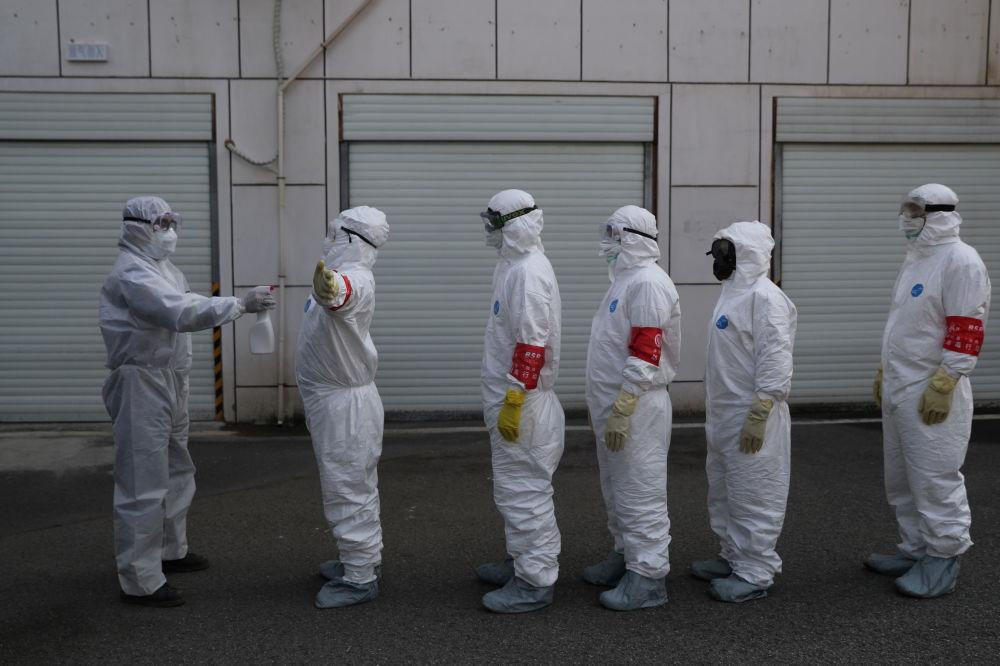 Тем временем в Китае продолжают бороться с опасным заболеванием. На снимке - волонтеры в защитных костюмах проходят дезинфекцию в Ухане, эпицентре вспышки коронавируса в провинции Хубэй, Китай