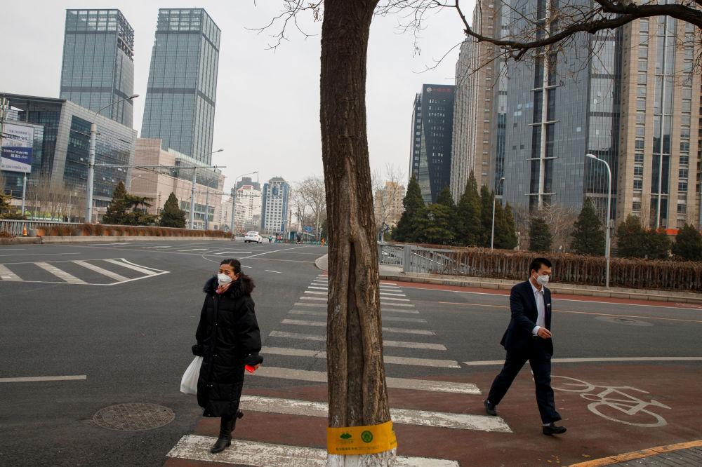Тем временем улицы китайских городов, обычно переполненные, опустели. На снимке - жители Пекина идут по пустым улицам в масках, опасаясь коронавируса