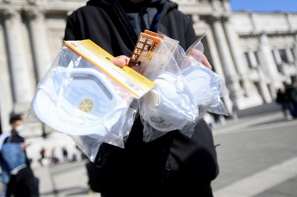 На улицах итальянских городов начинает расцветать торговля масками и средствами защиты от коронавируса. На снимке - уличный торговец в центре Милана предлагает приобрести у него одноразовые респираторы