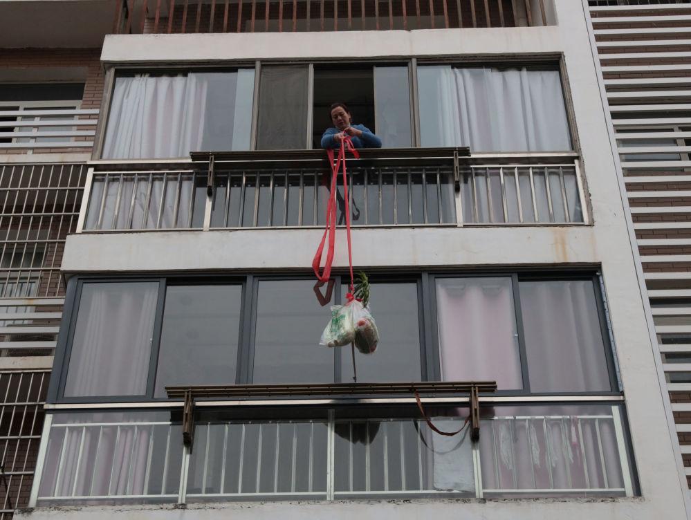 В самом Китае карантину подверглись целые города. Их жители не покидают пределы домов. На снимке - жительница провинции Хубэй в Китае поднимает к себе домой продукты на веревке