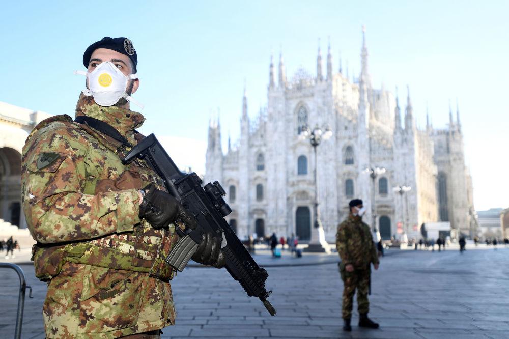 Тем временем на улицы Милана власти вывели военных в защитном снаряжении и с оружием для обеспечения порядка. На фото - военные дежурят у миланского собора Рождества Святой Девы Марии, закрытого после вспышки коронавируса  в Италии