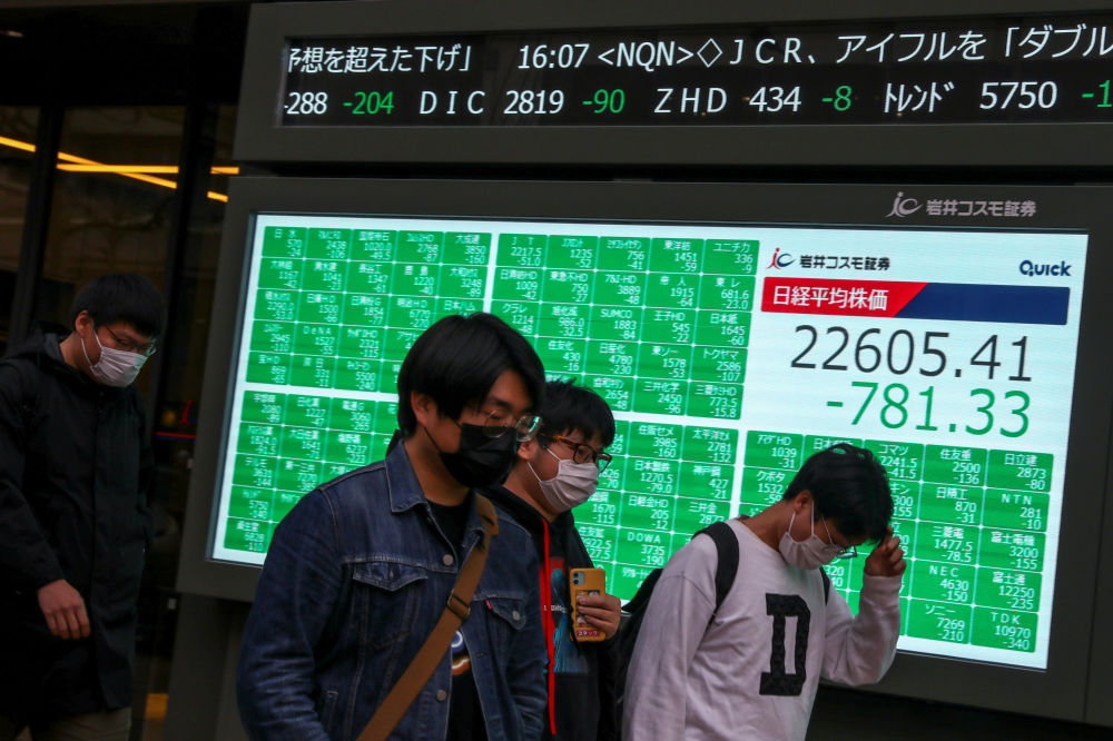 Биржевые индексы на фоне роста паники и распространения коронавируса по миру продолжают падать. На снимке - жители Японии в масках идут по улице в Токио мимо экрана, который показывает биржевые индексы