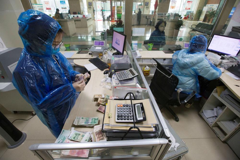 В самом Китае ношение защитных масок и одежды уже стало обязательным. На снимке - так работают сотрудники одного из банков в городе Тайюань, провинция Шаньси. Такая защита должна помочь им не заразиться коронавирусом