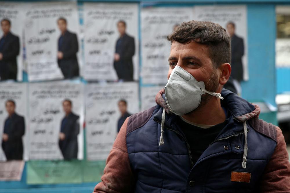 В Иране тоже зафиксировано около 100 случаев коронавируса. В таких условиях в стране состоялись парламентские выборы. На снимке - житель Тегерана на фоне избирательных плакатов