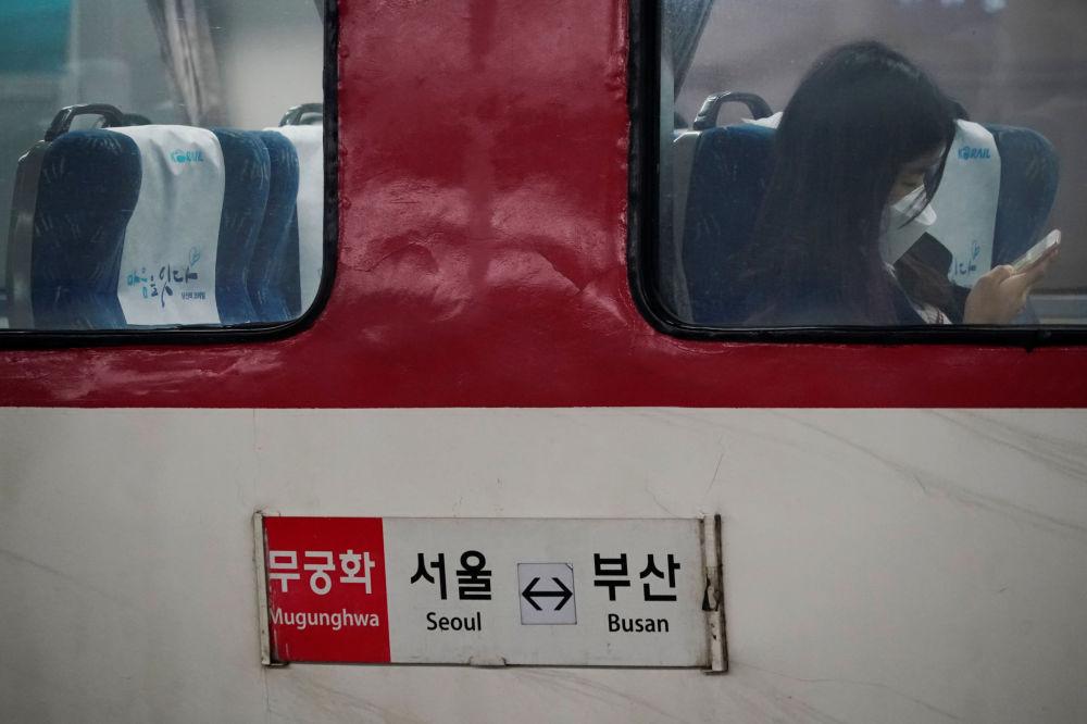 Грустная картина. Девушка в маске едет в метро в Сеуле, Южная Корея, опасаясь коронавируса. В этой стране зафиксировано уже около 1000 случаев заболевания