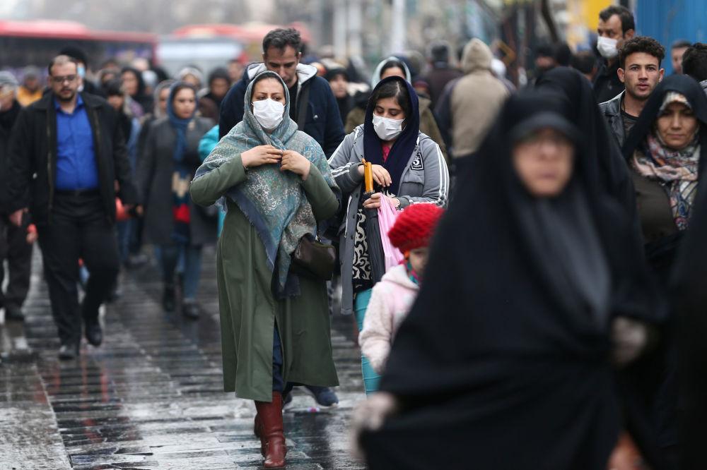 Жители Ирана идут по улице Тегерана в масках, опасаясь коронавируса. Хотя тут пока гораздо меньше случаев, чем к примеру, в Японии - 100 против 160, но медицина не так развита. Поэтому на 100 заболевших пришлось 16 погибших