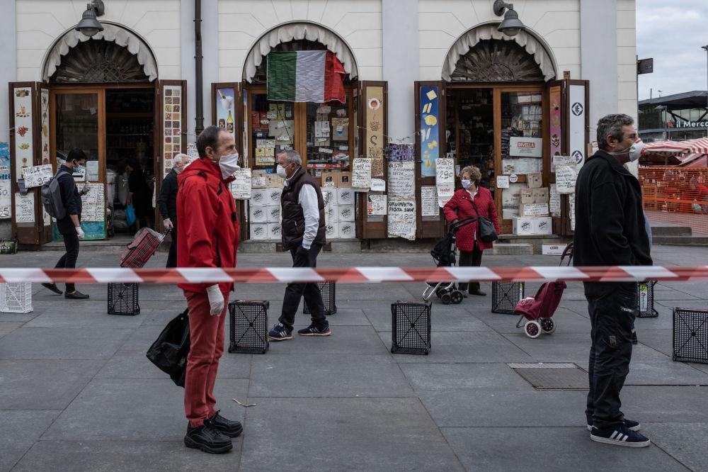 مردم در حال رعایت فاصله اجتماعی در صف بازارچه مواد غذایی در تورین ایتالیا