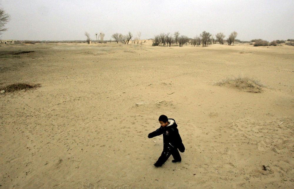 کودک در حال راه رفتن  در کویر شنی در استان گانسو چین که کشاورزی  غیر معقولانه در آنجا باعث پیشروی کویر شده است.